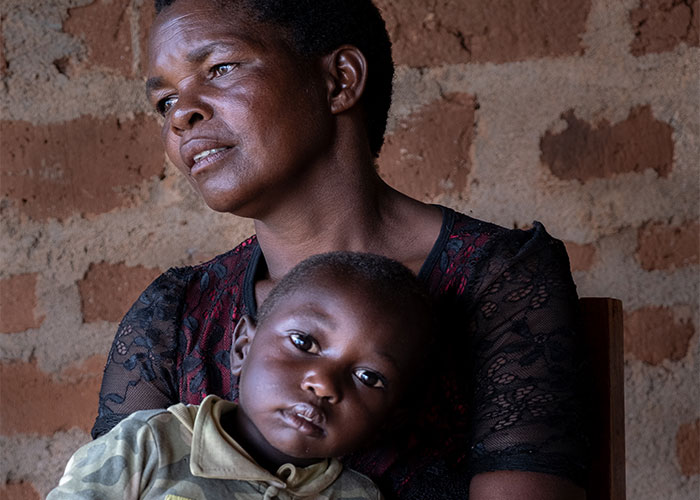 Maria carrying her son Christopher who have been supported by Action Against Hunger's programme in Tanzania