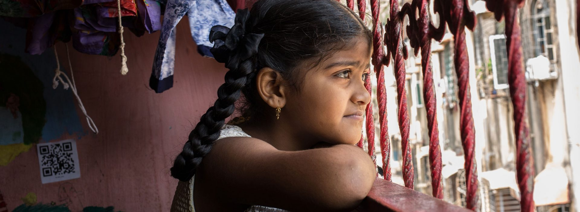 A young girl looks out of the window in India