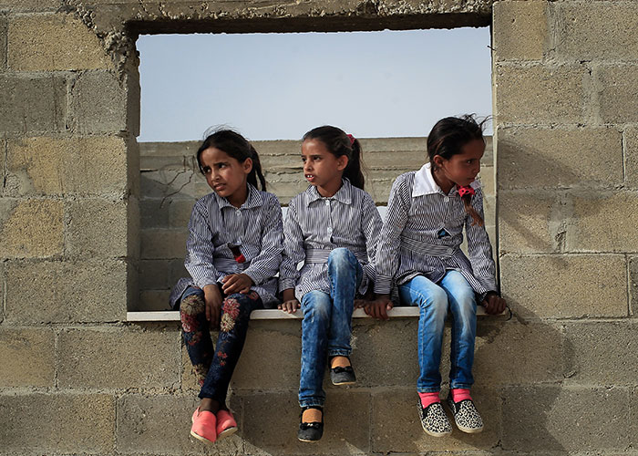 Palestinian children sitting on a wall in a desert
