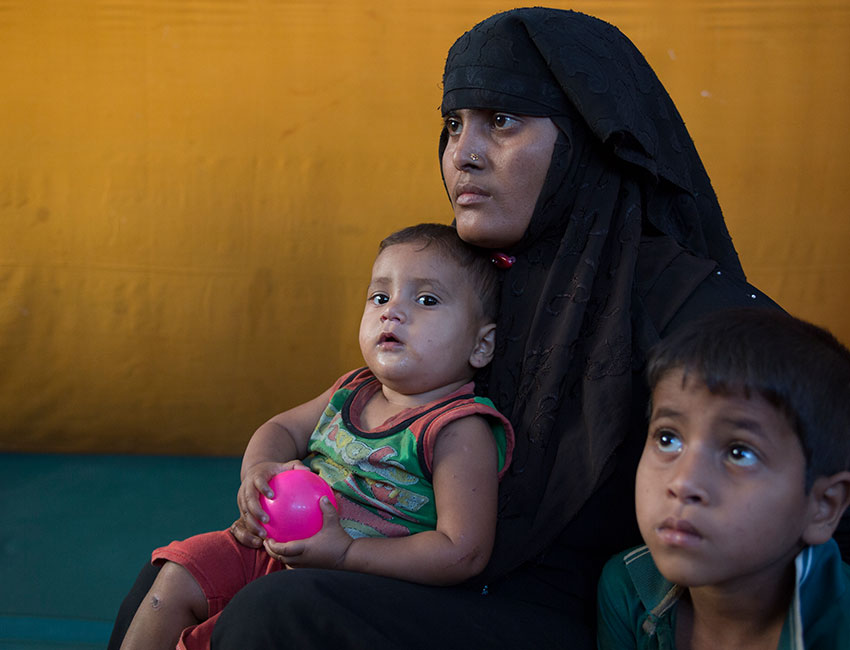 Setara Begum sits with her Children Ashmila Bibi and Yasmun as other children are cared for in Action Against Hunger's child friendly space