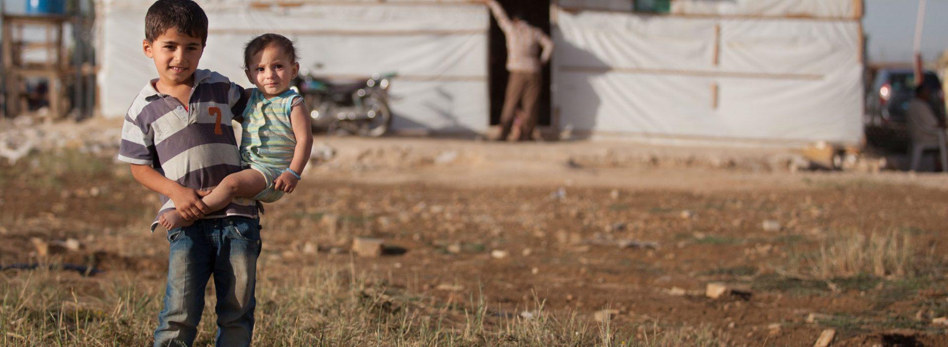 Refugee children standing in a camp