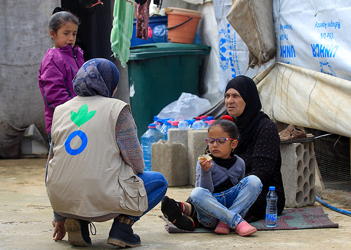 Olfat Mohamed, an Action Against Hunger Water and Sanitation team member speaking to Syrian refugees in a camp