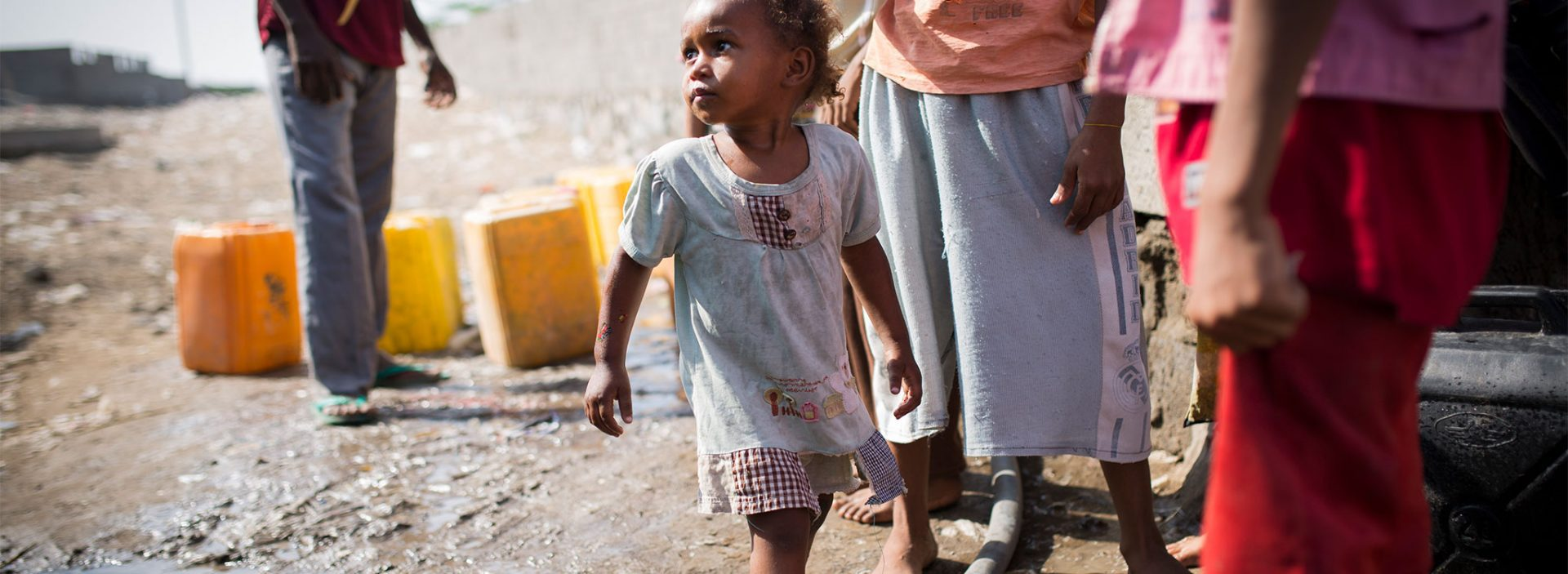 Young Yemeni girl standing with lots of water cans as her family collects water from pumps