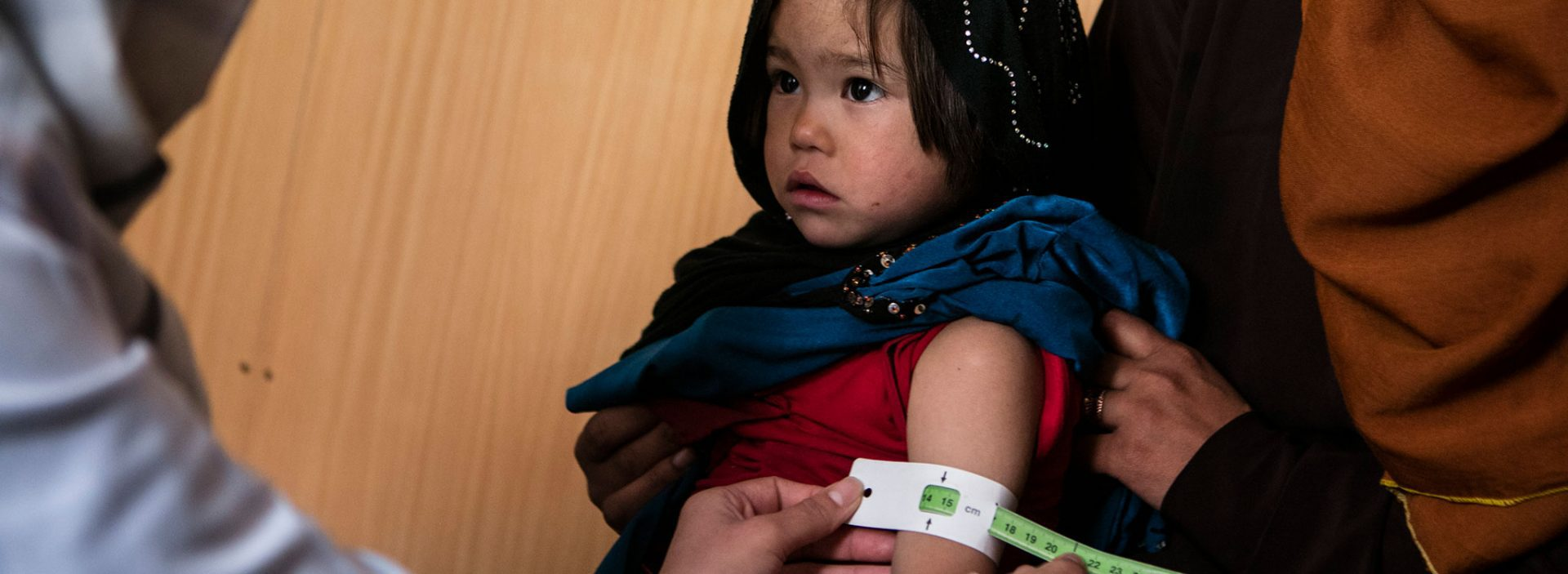 A girl in Afghanistan is screened for malnutrition using a MUAC band.