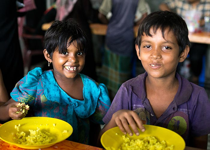 Two children enjoy a meal provided by Action Against Hunger.