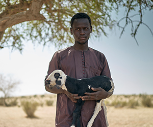 A man holds a goat at an Action Against Hunger project in Chad.