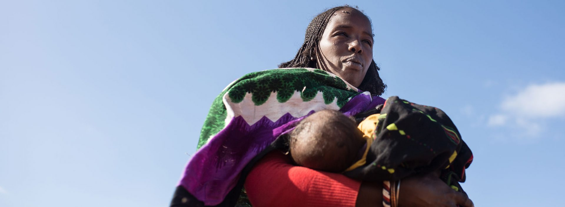 A woman carries their child at an Action Against Hunger project in Ethiopia.
