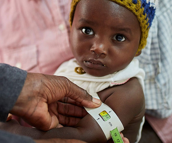 A child is screened for malnutrition using a MUAC band at an Action Against Hunger treatment centre in Haiti.