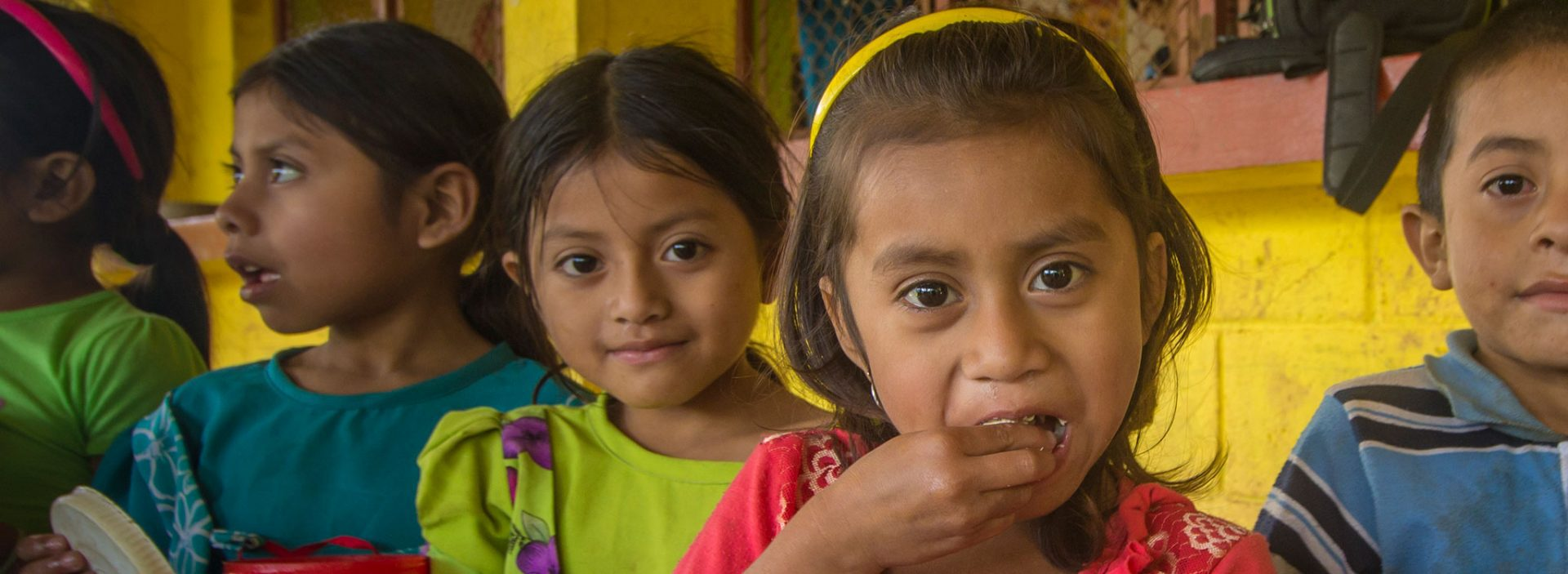 A girl eating food at an Action Against Hunger project in Guatemala.