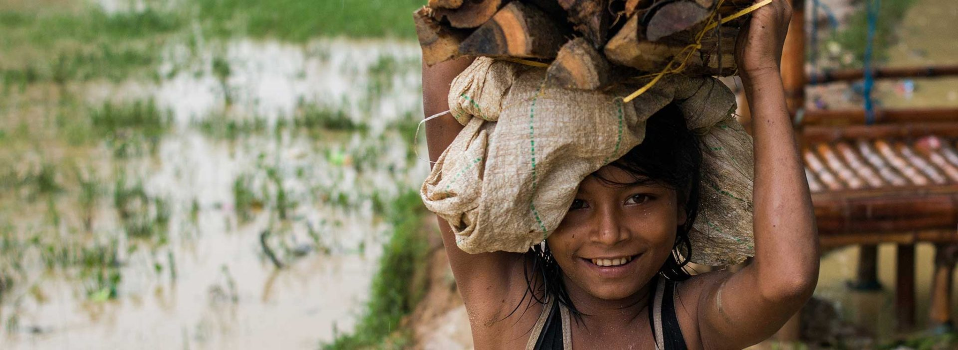 A Rohingya refugee from Myanmar helped by Action Against Hunger carries some wood.
