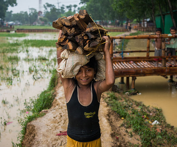 A Rohingya refugee carrying logs.