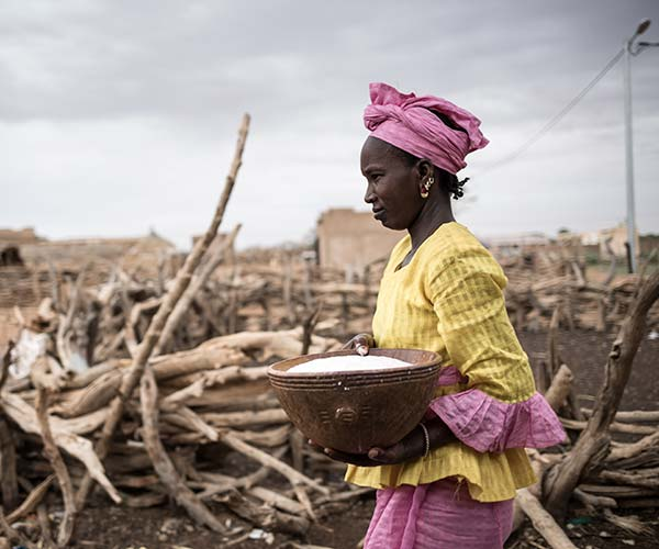 A woman carries a bowl of milk in Senegal.