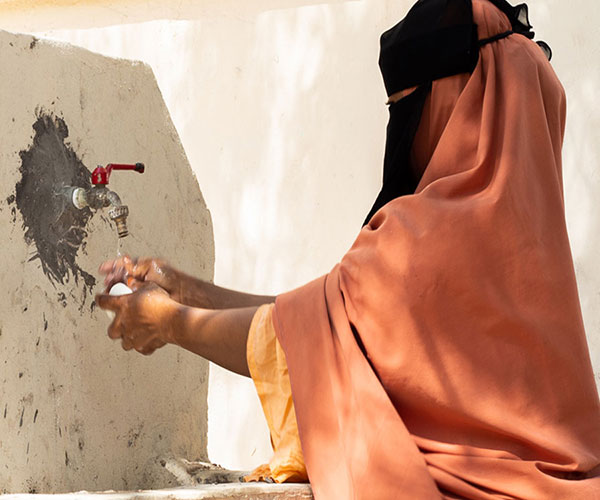 A woman washes her hands at an Action Against Hunger health centre in Somalia.