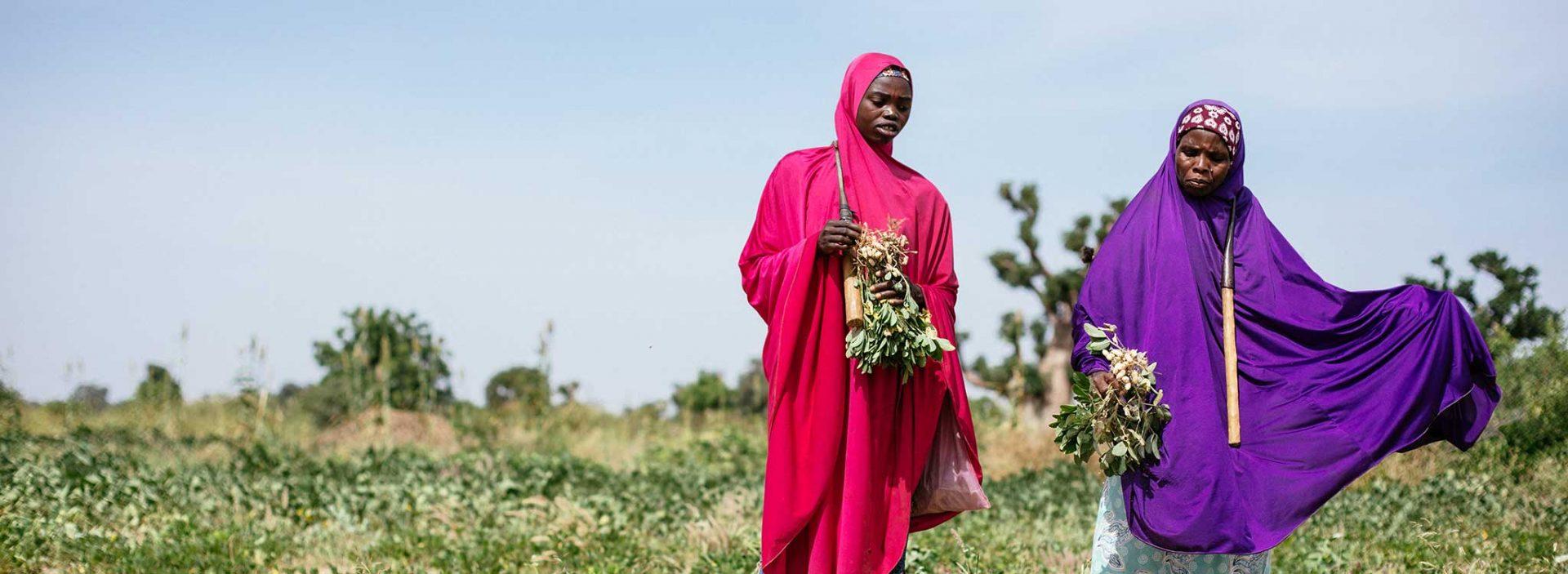 Two women in a field in Nigeria.