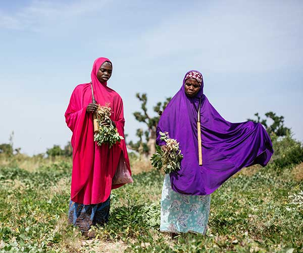Two women in a field in Nigeria.