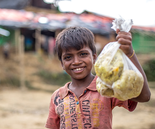 Muk collects bag of rice at an Action Against Hunger distribution centre in Bangladesh.