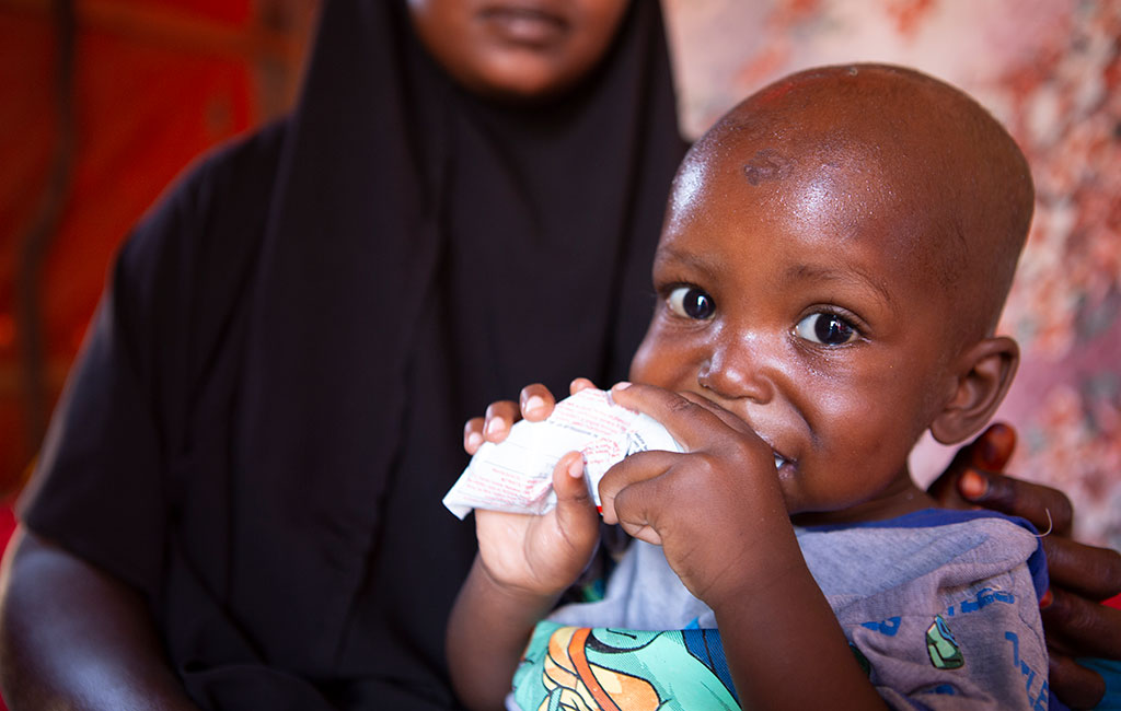 Mohamed eats ready-to-use therapeutic food provided by Action Against Hunger at his home in Mogadishu, Somalia.