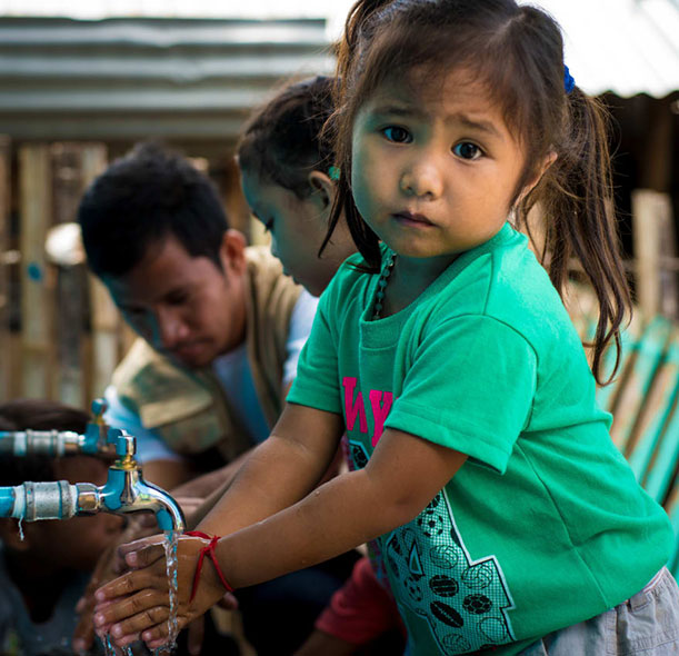 A girl washes her hands in the Philippines.