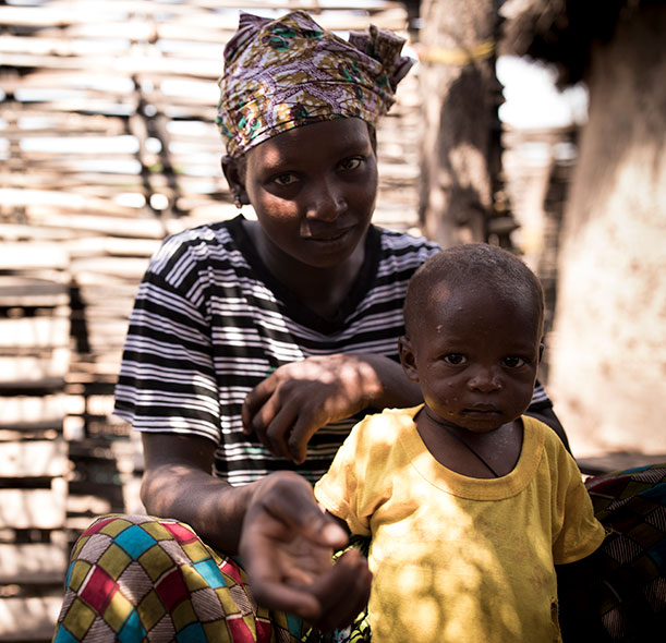 Simbo, a boy who recovered from malnutrition thanks to support from Action Against Hunger, with his mum in a village in Mali.