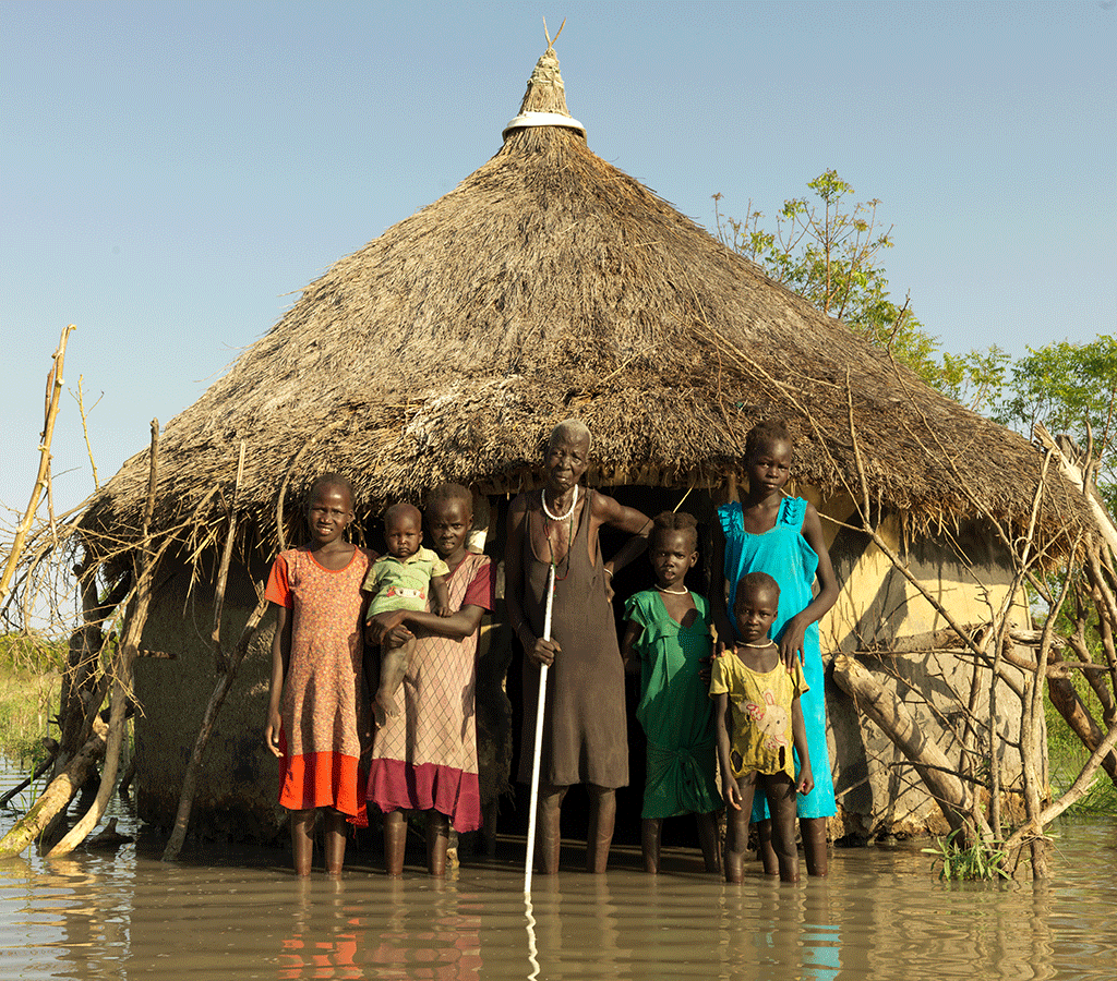 Nyabiele Chan, 80, from Pathiey Village stands by her flooded home with her grandchildren in South Sudan