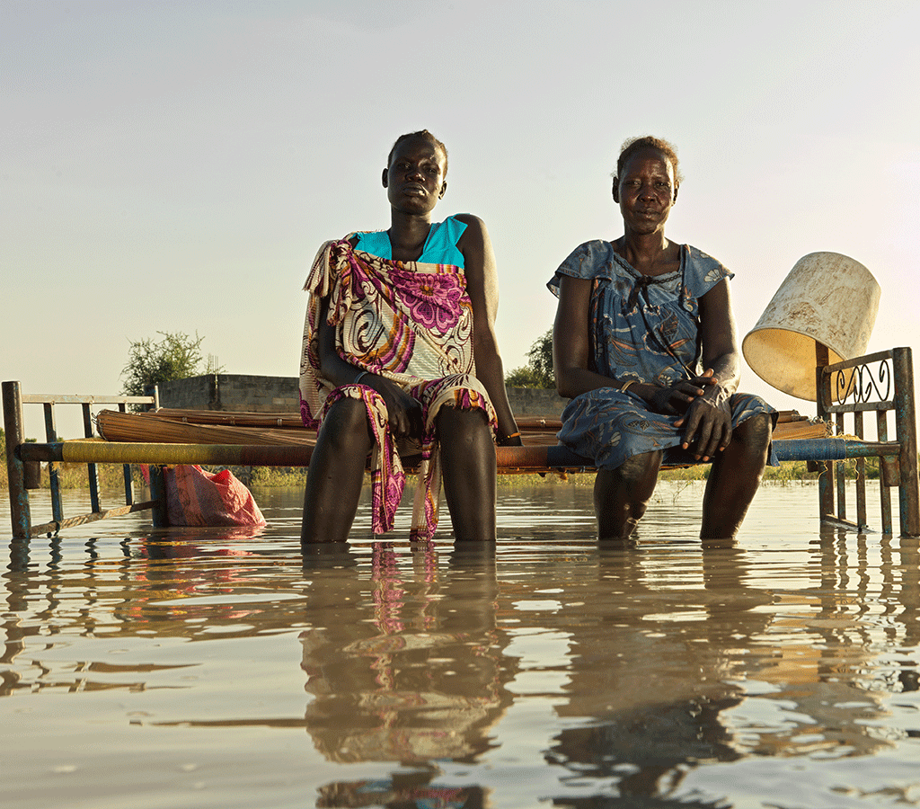 Nyagout Lok, 46, and her pregnant daughter, Nyakoang Majok, 28, set up a bed in the water – there is no room for both of them to sleep inside their temporary shelter.in South Sudan
