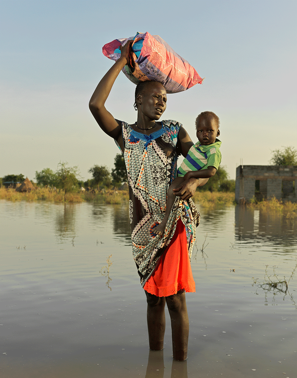 Nyapini Long, 30, heads to find higher ground with all her belongings in South Sudan