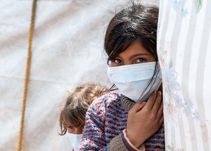 Bushra wears a mask in Al-Harakat Camp in Idlib, Syria.