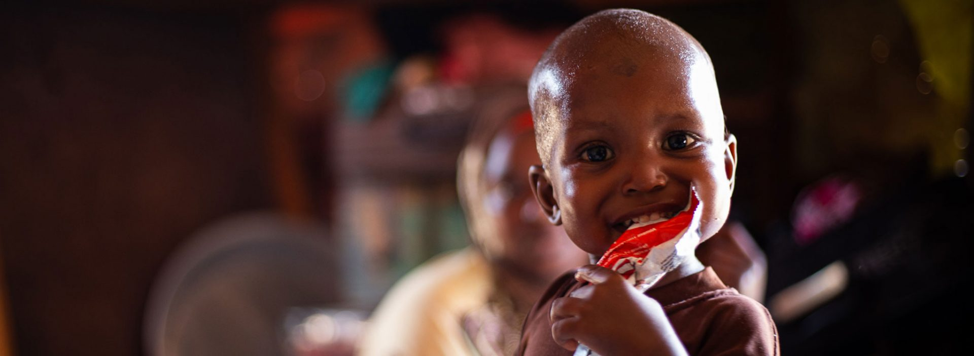 Mohamed from Mogadishu, Somalia, eats ready-to-use therapeutic food at home after receiving treatment for malnutrition from Action Against Hunger.