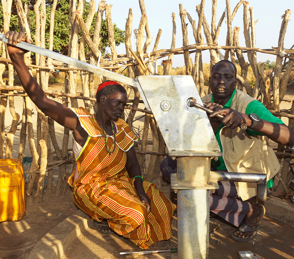 John from Action Against Hunger teaches Nyanut how to repair the borehole at Baackuel Village, Malualkon, South Sudan.