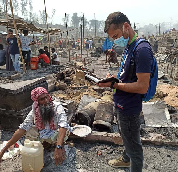 An Action Against Hunger staff member helps a man affected by the fires at a Rohingya refugee camp in Cox's Bazar, Bangladesh.