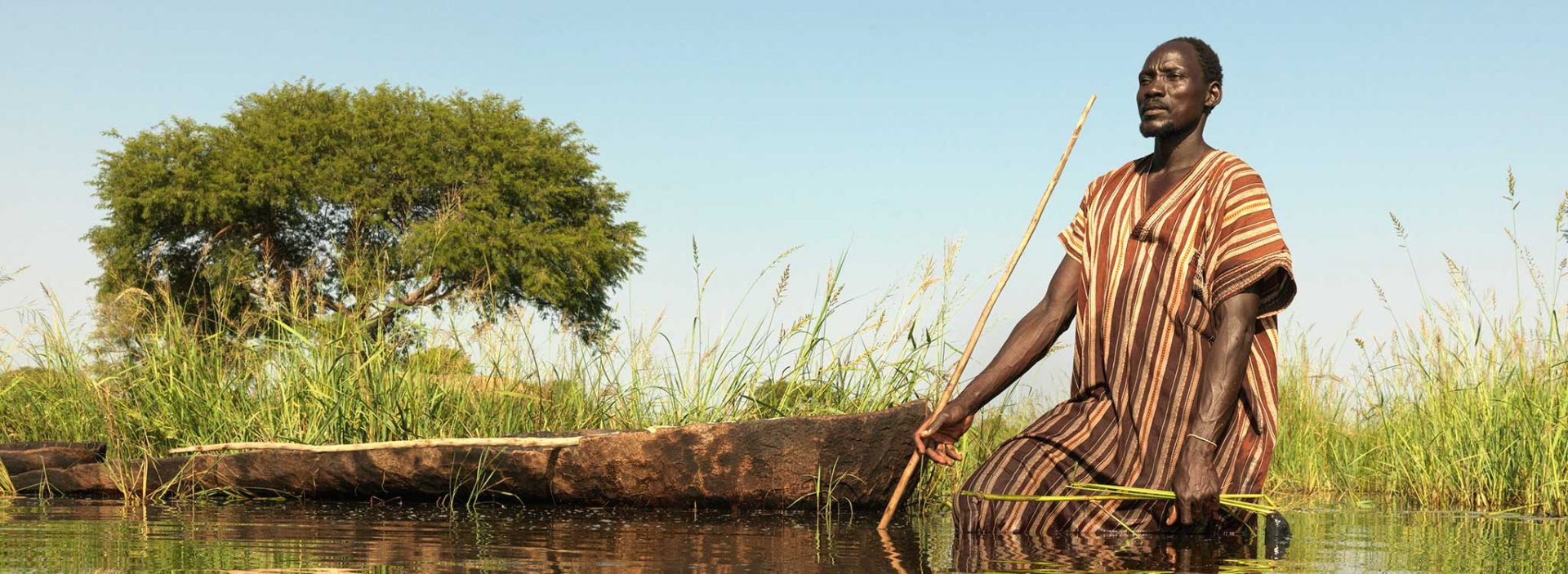 Gai tries to spear fish after his village in South Sudan is flooded.