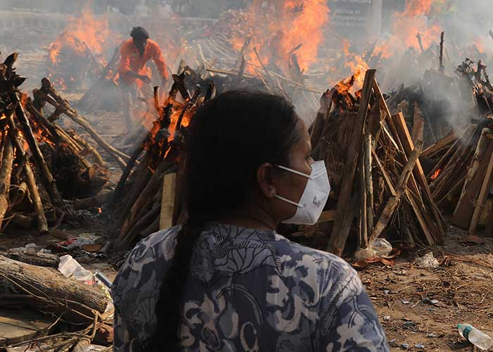 A family member looks on at funeral pyres of victims of coronavirus in India.
