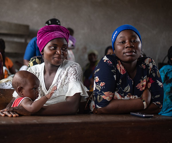 Esther with her eight-month-old daughter and Micheline during a mental health session at a school in Kichanga, DR Congo.