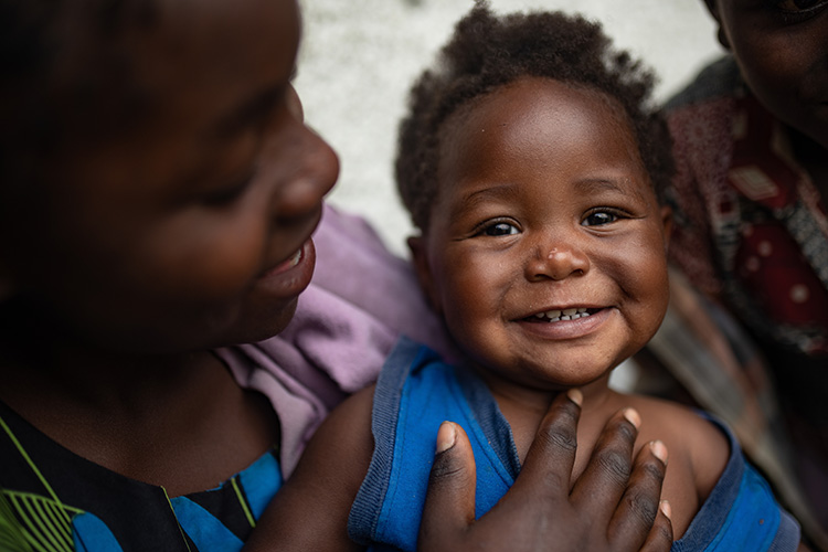 A picture of a smiling girl called Olivine. She's been supported by Action Against Hunger's projects in the Democratic Republic of Congo.