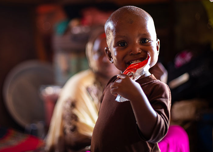 Mohamed eats ready-to-use therapeutic food at an Action Against Hunger stabilisation centre in Mogadishu, Somalia.